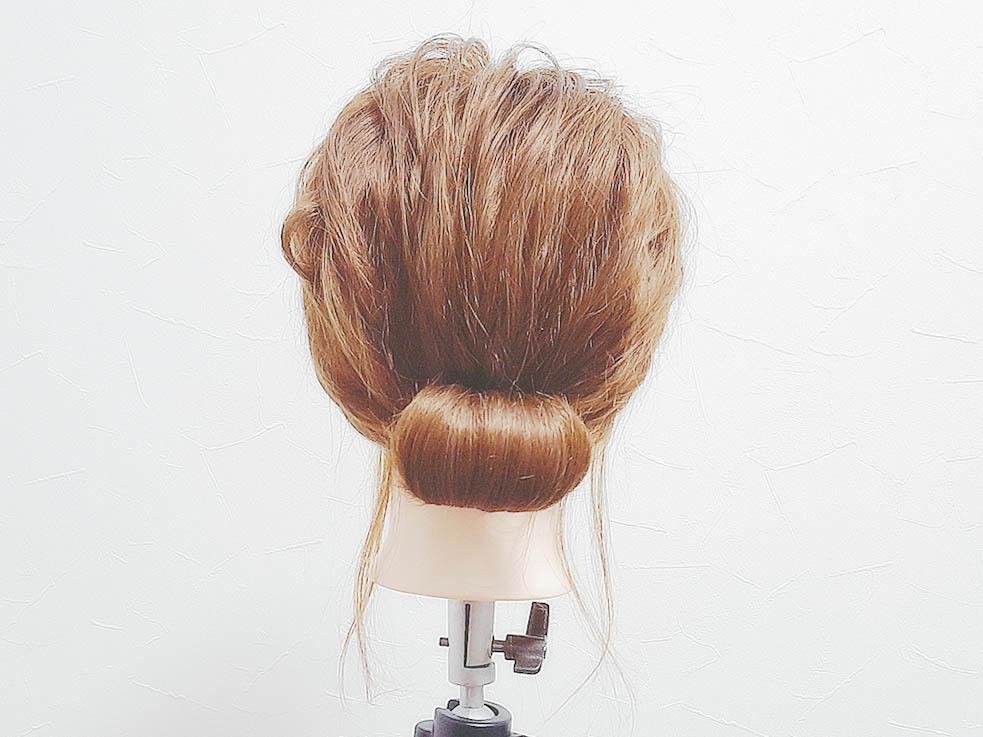 結んだ毛束の先を外巻きにくるくると巻いていきシニヨンを作り、アメピンを使って固定します