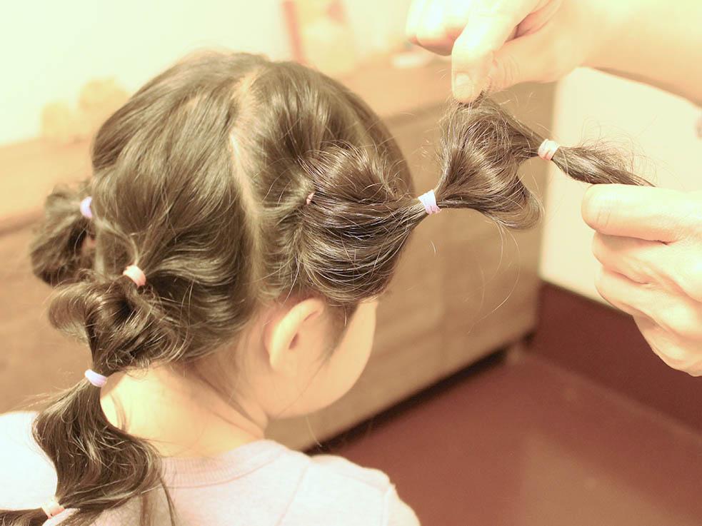 ②2~3cmほど間隔を空けてゴムで結び、髪を引き出して玉ねぎのような丸い形をつくっていきます。